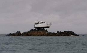 قارب معلق على صخرة في عرض البحر.. ما قصته؟