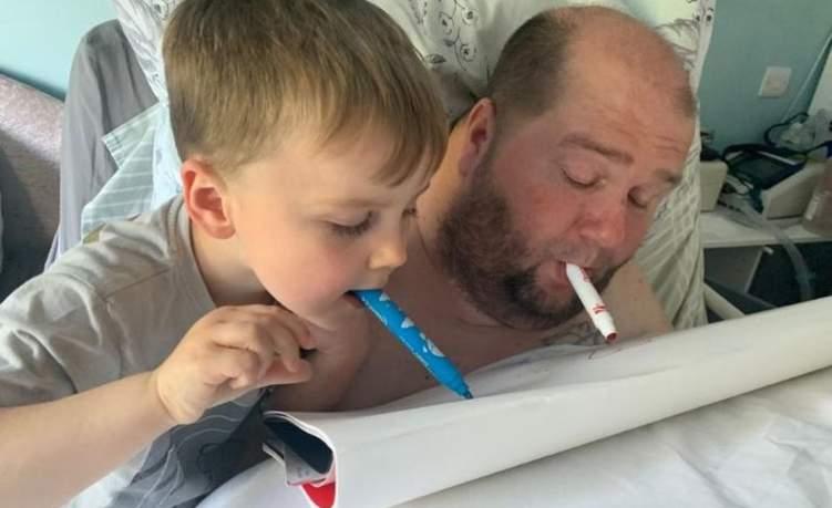 """بالصور: أب """"مشلول"""" يعلم ابنه الرسم بالفم"""